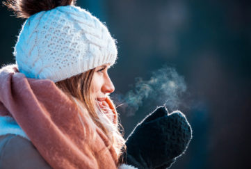 Woman breathing on her hands to keep them warm at cold winter day;