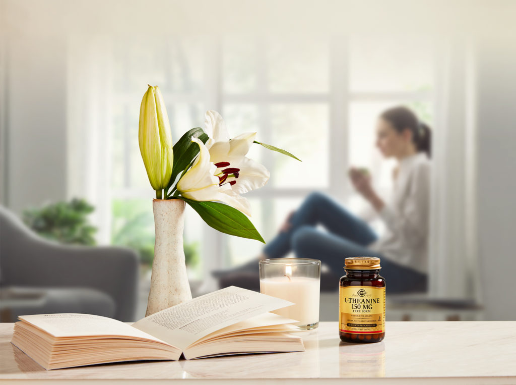 Woman sits by window with cup. In foreground are a vase of lilies, an open book and a bottle of Solgar vitamins