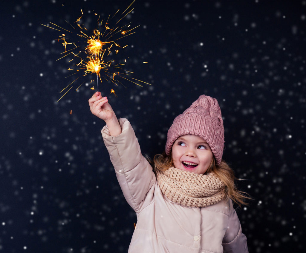 Dogs and fireworks: little girl in a knitted pink hat holding sparkler