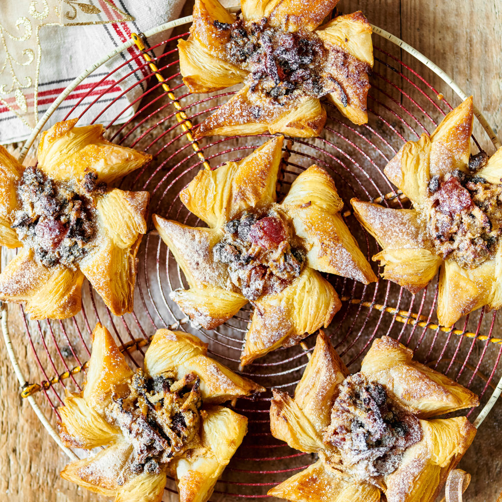 Circular wire rack with star shaped fruit-filled pastries dusted with icing sugar