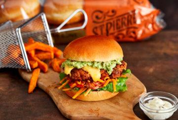 Gourmet burger in brioche bun with orange pumpkin slaw and sweet potato fries
