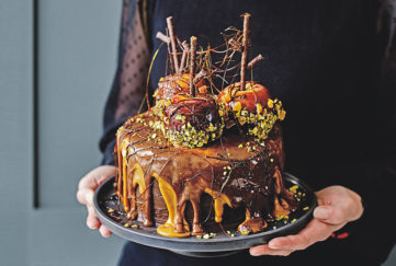 "Woman's hands holding plate with cake, drips of caramel and chocolate icing, 3 toffee apples coated in pistachios, spun sugar ""cobwebs"" between the chocolate sticks"