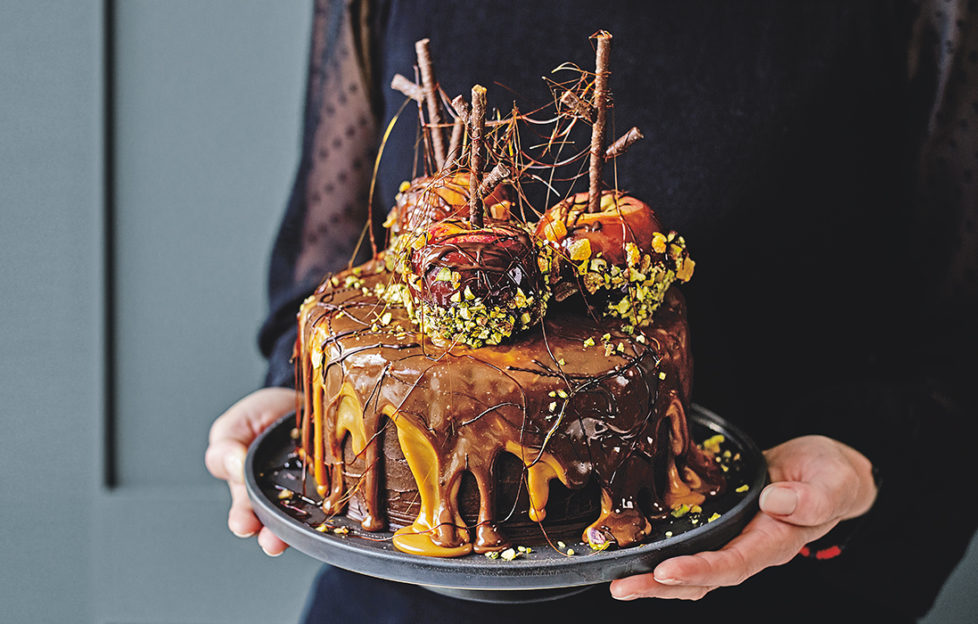 """Woman's hands holding plate with cake, drips of caramel and chocolate icing, 3 toffee apples coated in pistachios, spun sugar """"cobwebs"""" between the chocolate sticks"""