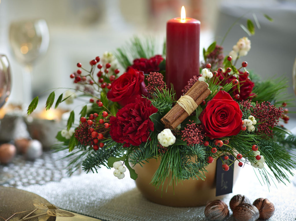 Red flowers in a candle arrangement
