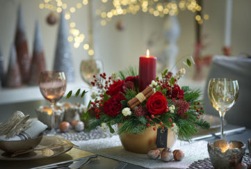 Flowers in a candle arrangement on a Christmas table