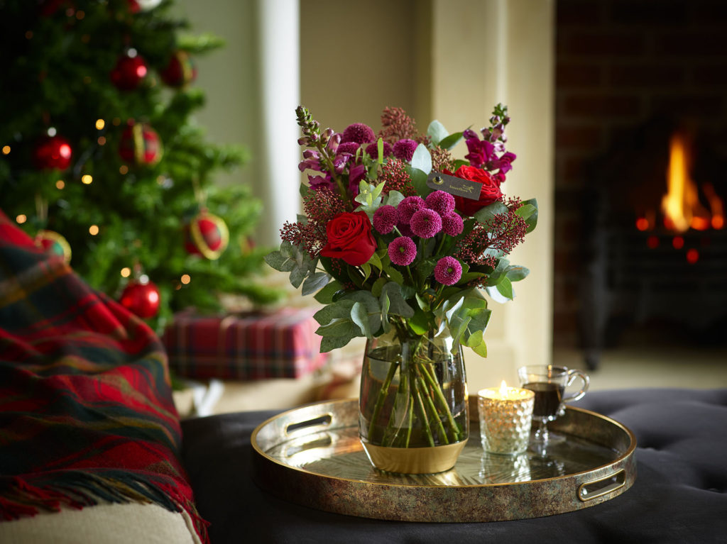 Bouquet of flowers in vase in Christmas decorated room