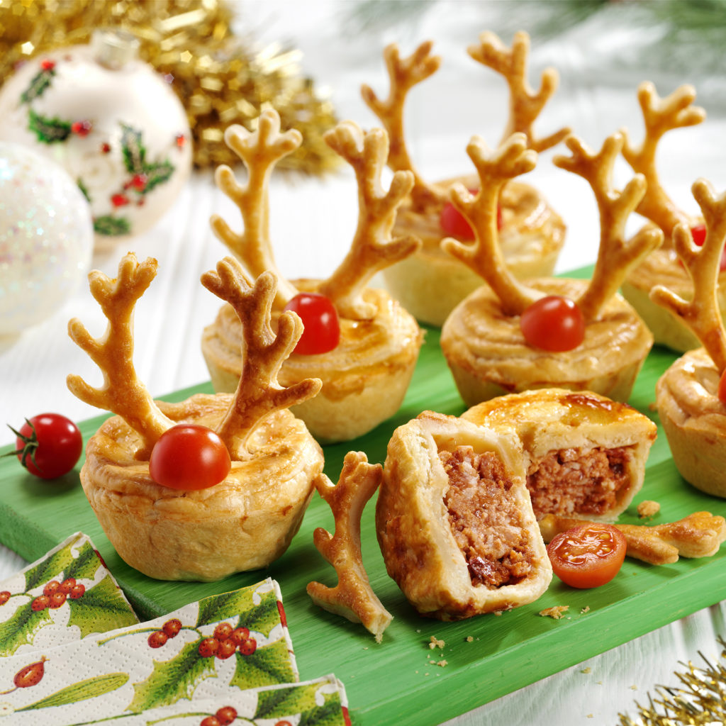 7 small meat pies on a green board, decorated with pastry antlers and half a cherry tomato