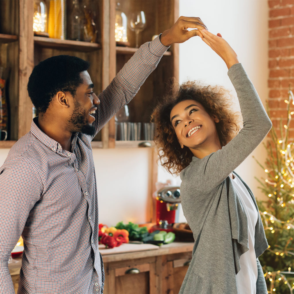 Happy couple dancing in kitchen at home, Christmas tree in the background