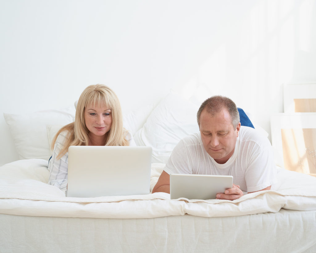 Mature married couple planning travel, choosing vacation, looking for tickets, booking hotel. Handsome man with tablet and attractive middle age woman with laptop spending time together