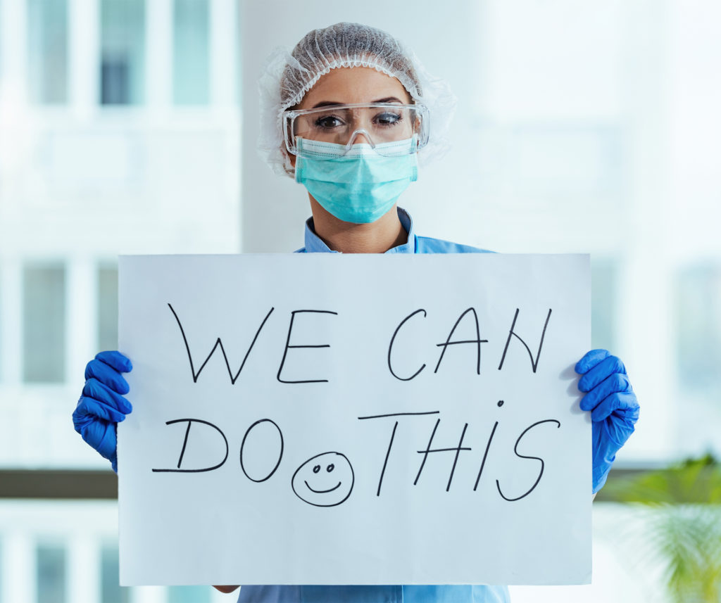 NHS nurse in mask and PPE holds up sign, We Can Do This