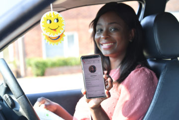 Smiling woman in car holds up phone showing NHS responder app