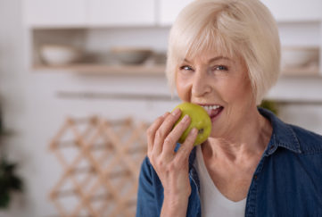 Older woman eating an apple in her kitchen