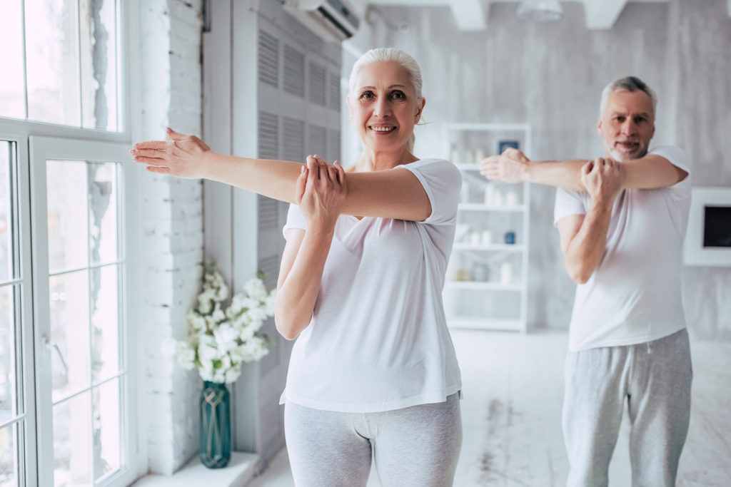 Senior couple is doing fitness training at home. Doing yoga together.