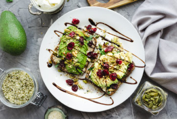 Healthy avocado toasts for breakfast or lunch with rye bread, cream cheese, arugula, sliced avocado, dried cranberry, pumpkin, hemp and sesame seeds. Vegetarian sandwiches. Clean eating