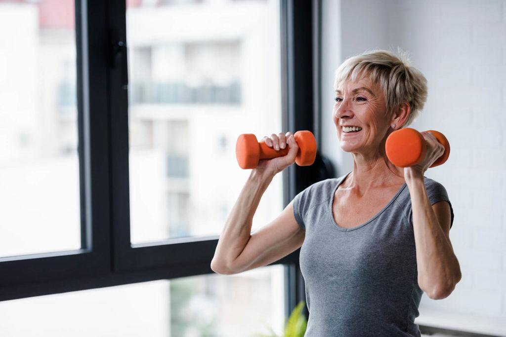 Portrait of senior woman lifting dumbbells;