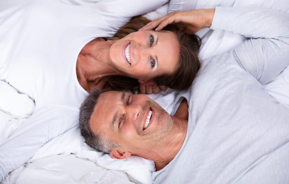 High Angle View Of Happy Mature Couple Lying On Bed;