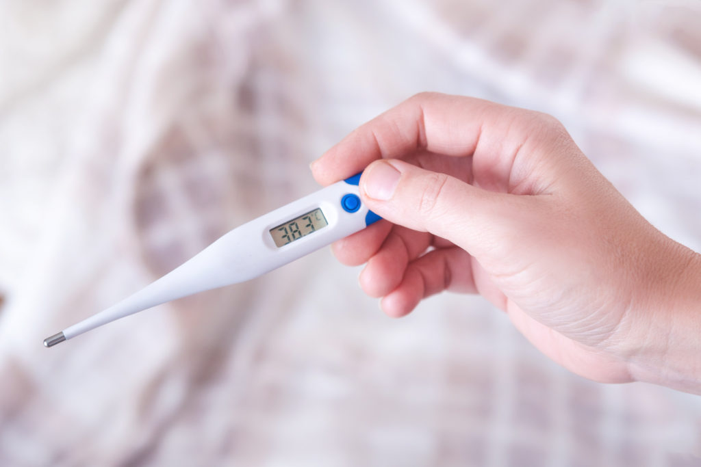 Closeup shot of a woman looking at thermometer. Female hands holding a digital thermometer. Girl measures the temperature. Shallow depth of field with focus on thermometer.;