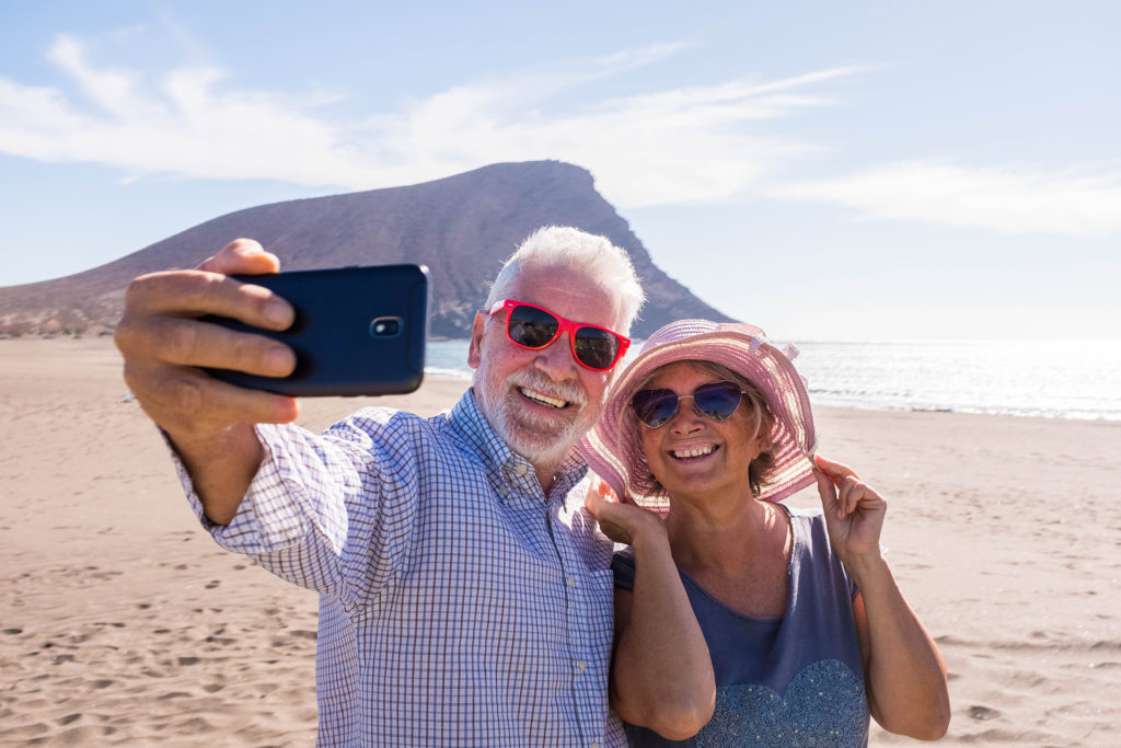 couple of two seniors takign a selfie together at the beach having fun in their vacations - happy mature old people smiling and looking at the camera of the phone