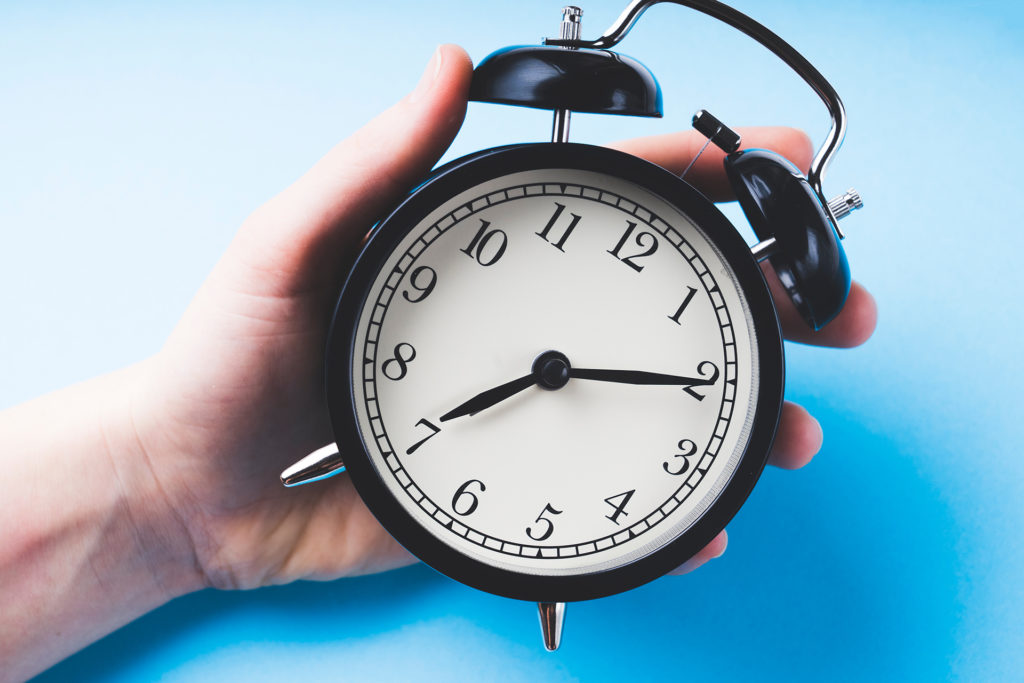 sets the alarm, women's hands set the time and set the alarm on a black vintage alarm clock , concept, selective focus, tinted image on a blue background;