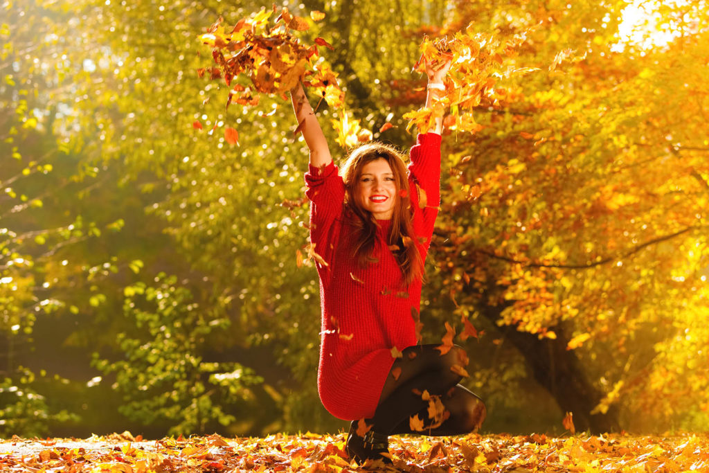 Happiness carefree. woman relaxing in autumn park throwing leaves up in the air with arms raised up. Beautiful girl in colourful forest foliage outdoor.;