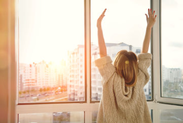 Woman near window raising hands facing the sunrise at morning;