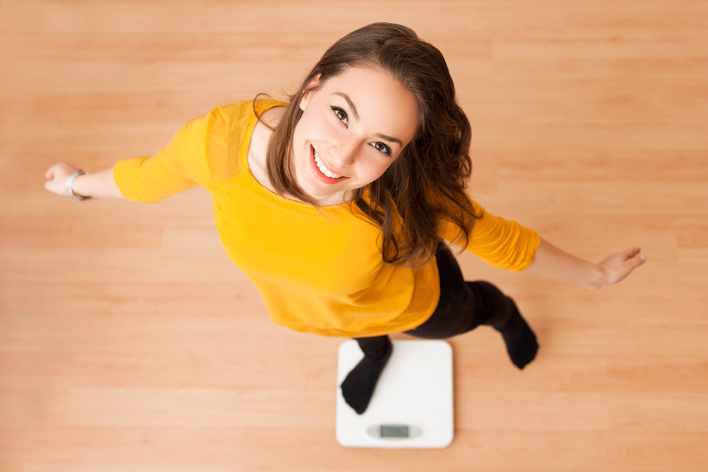 Portrait of young brunette beauty using household scale.;