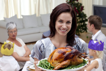 Woman showing Christmas turkey for family dinner at home;