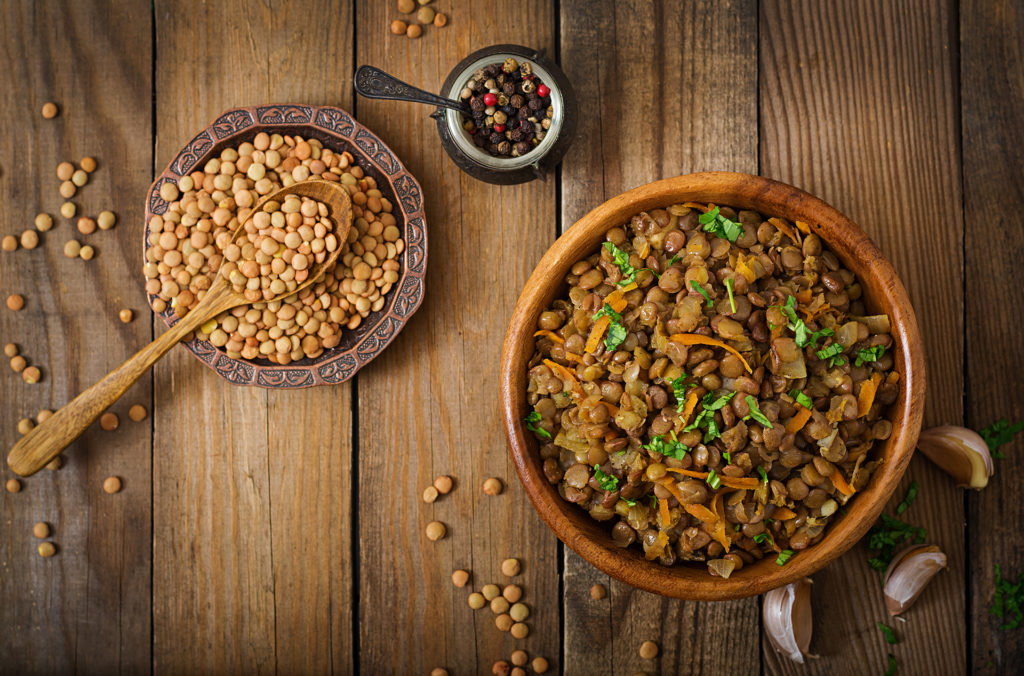 Lentil with carrot and onion in wooden bowl. Healthy lifestyle. Diet menu. Flat lay. Top view;
