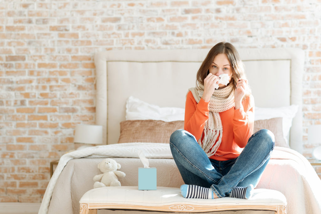 Upset young woman suffering from influenza at home;