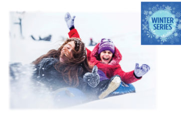 2 teenage girls sledging down a hill laughing, one in red, one in blue
