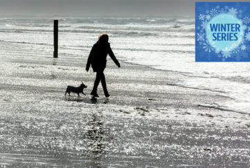 Woman and dog walking along wintry seashore