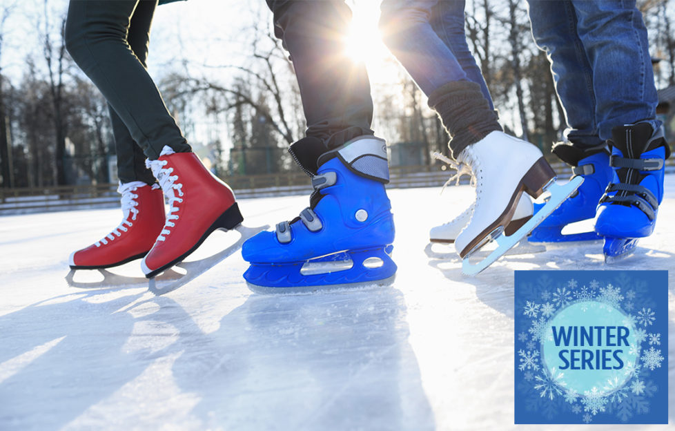 Feet of 4 ice skaters on lake, figure skating boots and ice hockey boots, sun through trees behind