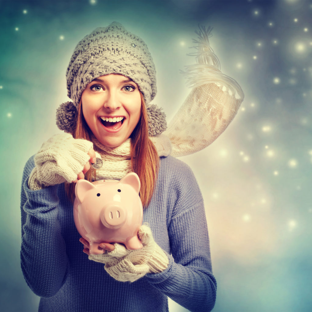 Woman in cosy hat and scarf posting coin into piggy bank - Christmas savings