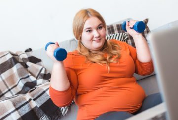Chubby woman lifting dumbbells to be healthierimprove fitness