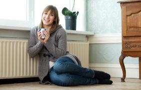 Woman with mug sits by radiator