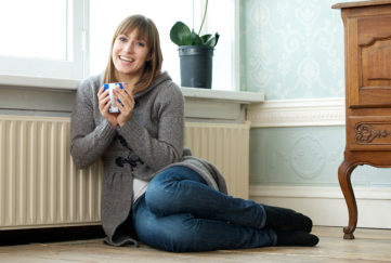 Woman with mug sits by radiator