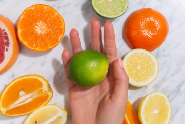 Hand with lime in it, surrounded by grapefruit, oranges and lemons.