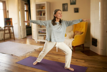 Full length shot of happy energetic mature woman in casual clothes exercising at home because of social distancing, practicing yoga on mat, standing in warrior ii pose. Age, wellness and health;