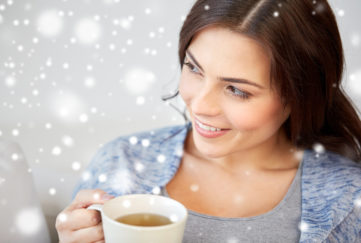 people, drinks, christmas and winter concept - happy young woman with cup of tea at home over snow;
