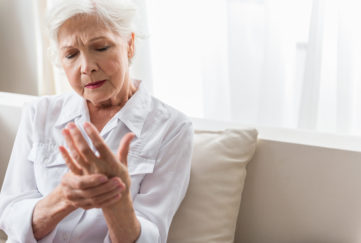 Older woman rubs painful hand.