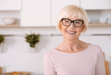 Enjoy home atmosphere. Nice cheerful aged woman smiling and standing in the kitchen;