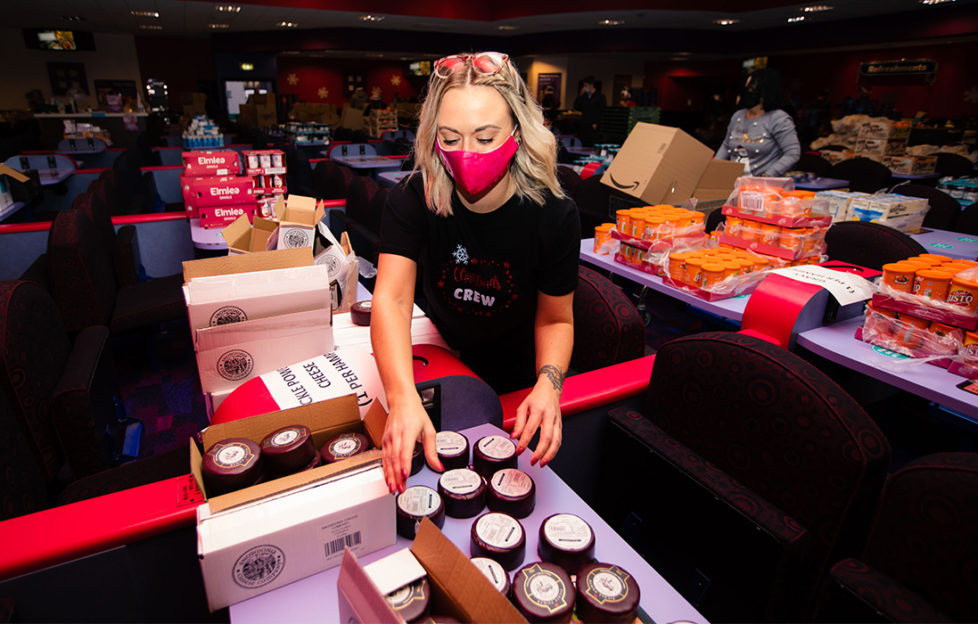 Woman in mask sorting goods for charity hampers