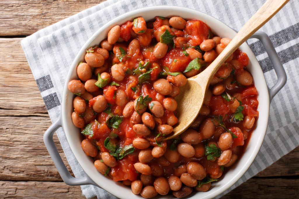 Organic Borlotti beans in tomato sauce with herbs close-up in a bowl on the table. horizontal top view from above ;