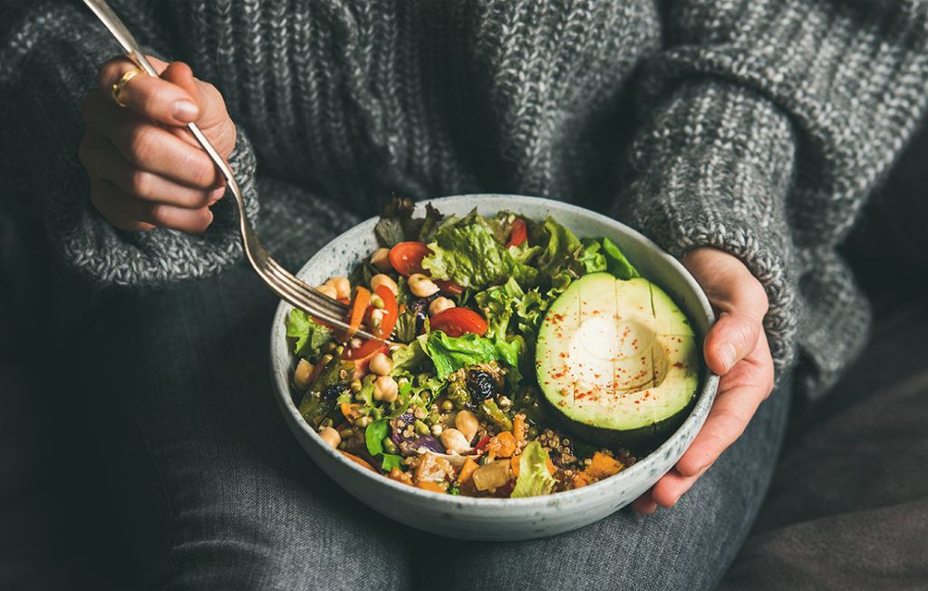 Healthy vegetarian dinner. Woman in jeans and warm sweater holding bowl with fresh salad, avocado, grains, beans, roasted vegetables, close-up. Superfood, clean eating, vegan, dieting food concept;
