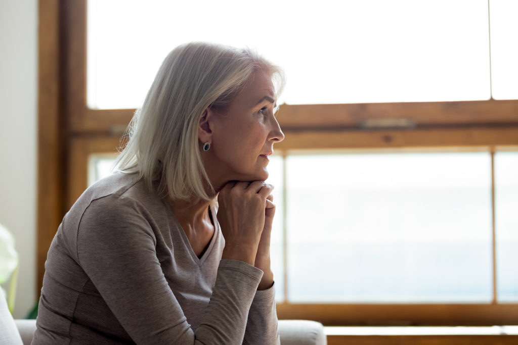 Side view of sad thoughtful middle-aged mature woman sit on couch at home look in window distance mourning, upset pensive senior female lost in thoughts thinking or pondering over past