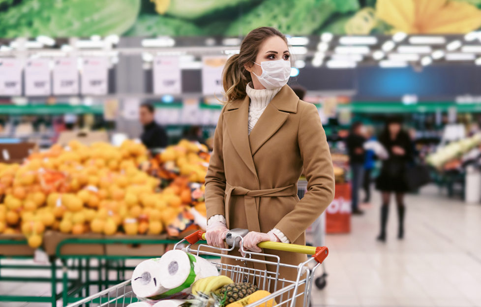 Shopping during the coronavirus Covid-19 pandemic. A young woman buys food in a supermarket with shopping cart. Woman in facial mask and gloves to prevent infection.;