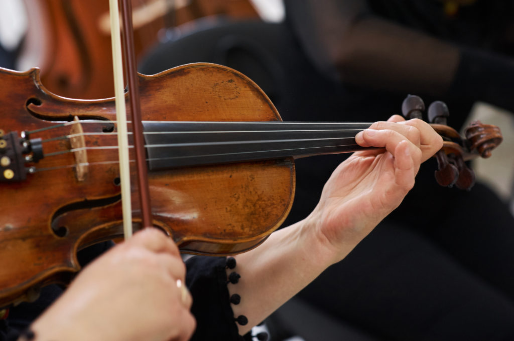 Women Violinist Playing Classical Violin Music in Musical Performance;