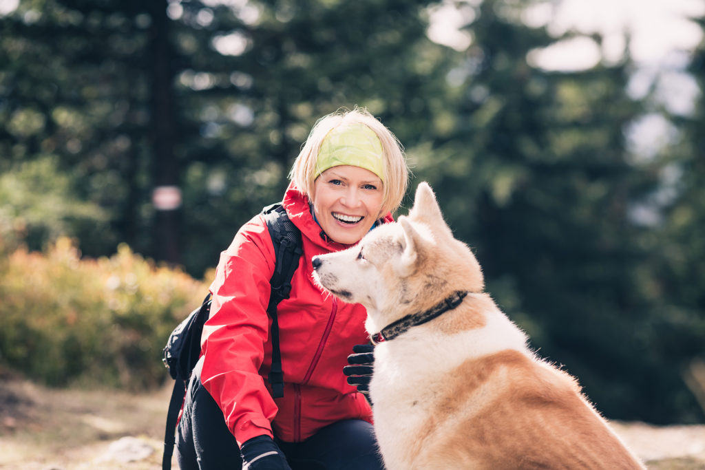 Woman hiking with akita inu dog on forest trail. Friendship, recreation and healthy lifestyle outdoors, autumn woods in mountains, inspirational nature. Fitness and trekking and activity concept.;