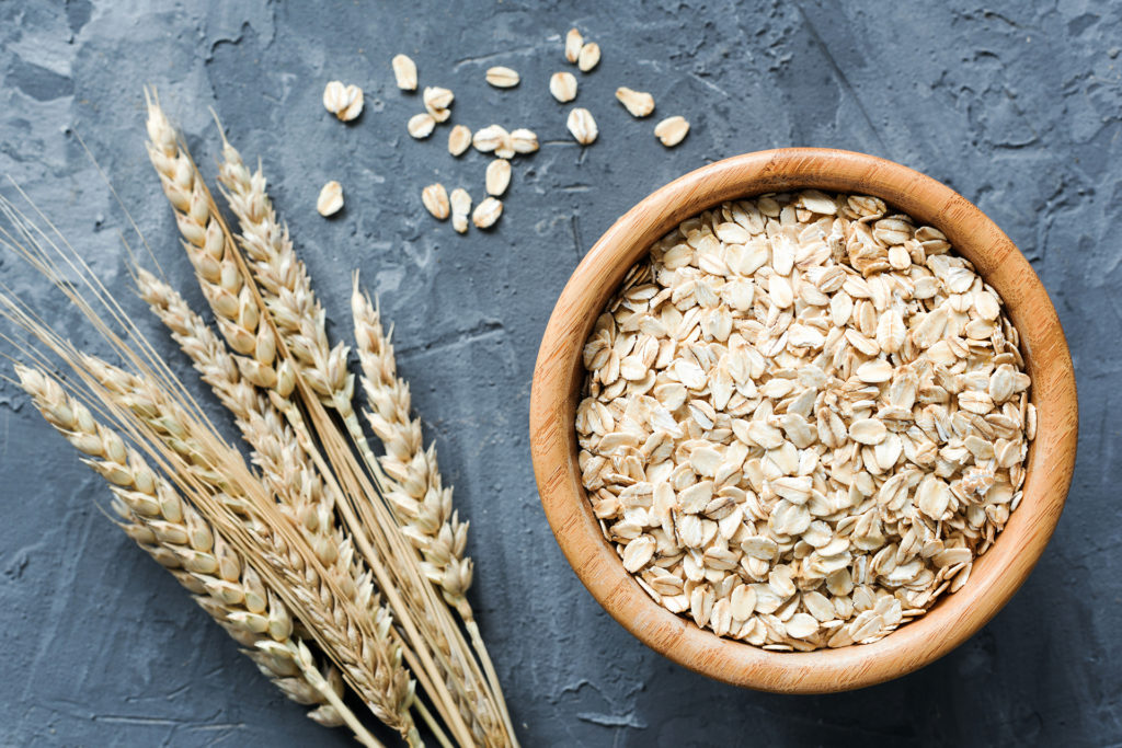 Oats in wooden bowl. Uncooked rolled oats. Oat flakes. Top view. Concept of healthy eating, dieting, healthy lifestyle, weight loss;