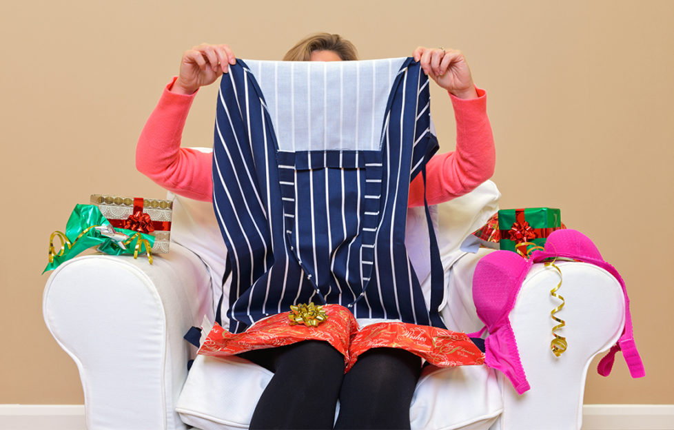 Woman opening unwanted gifts, apron and underwear. British Heart Foundation appeal for unwanted gifts